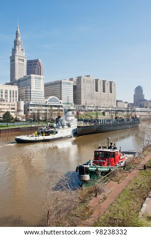 The 2012 Great Lakes shipping season gets underway as a tugboat and barge sail up the Cuyahoga River past the Tower City Complex in Cleveland, Ohio as a moored small tug awaits her next assignment