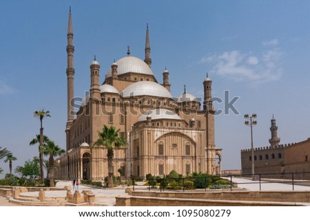 The Great Mosque of Muhammad Ali Pasha (Alabaster Mosque) situated in the Citadel of Cairo in Egypt in a daytime. A palm trees and a small garden at first plan.