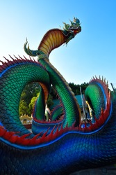 The great Naga or serpent statue has beautiful colors and has a sky background. Ancient animal statues according to Buddhist beliefs.
