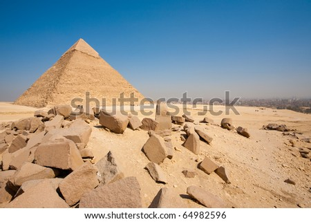 The Great Pyramid of Khafre and old building block boulders at the edge of Cairo city is visible in the distance with clear blue sky in the desert at Giza, Egypt. Horizontal copy space