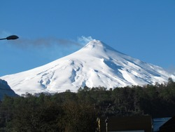 The great snowy volcano Villarrica with smoke at the top of the peak, in the city of Pucón in Araucania in Chile.