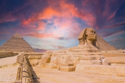 The Great Sphinx of Giza and in the background the Pyramids of Giza at sunset, the oldest funerary monument in the world. In the city of Cairo, Egypt