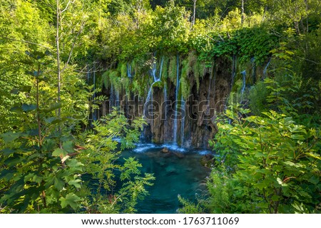Photo of  The Great Waterfall at Plitvice Lakes National Park in Croatia. Beautiful water cascade with river and lakes, popular tourist attraction worldwide. Stunning green waterfall in a forest in the summer