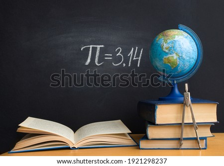 The Greek letter Pi the ratio of the circumference to its diameter, is drawn in chalk on a black school board with books, a globe and a compass in honor of the international number Pi for March 14 Zdjęcia stock ©