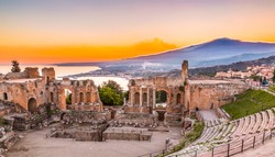 The  Greek Theater of Taormina as the Sun sets behind the smoking Etna, creating the beautiful colors inspiring the Hungarian Csontvary-Kcsztka Tivadar famous 1904-5 painting , Sicily, Catania, Italy