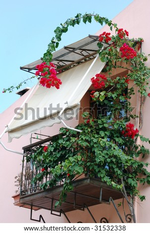 The green balcony with flowers around in Katakolon town, Greece.