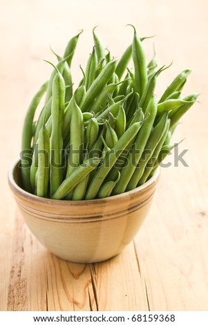 the green bean pods in brown bowl