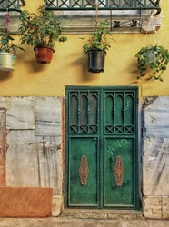 The green door of the house. Flowers in pots hung on the window. Yellow color wall.