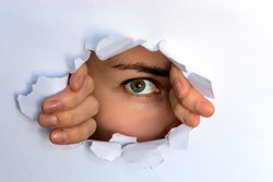 the green-eyed girl looking through torn paper. spying, glancing