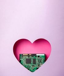 The green printed circuit board with microprocessors is located in a pink heart-shaped cavity. All around is purple. Copy Space. Love. Technology. Artificial intelligence. Robotics.