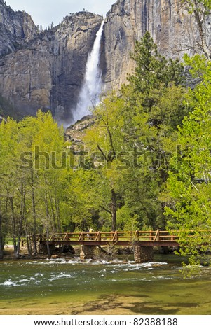 The green waters of the Merced River roll under the Sentinel Footbridge in front of Upper Yosemite Falls crashing down in its full Spring glory in Yosemite National Park, California