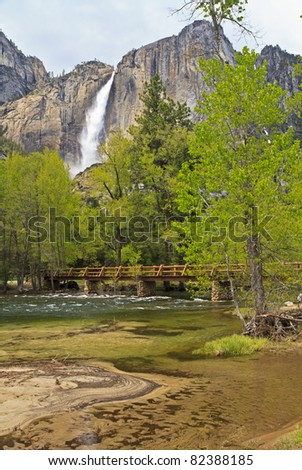 The green waters of the Merced River roll under the Sentinel Footbridge near a sandbar with Upper Yosemite Falls in the background in Yosemite National Park, California