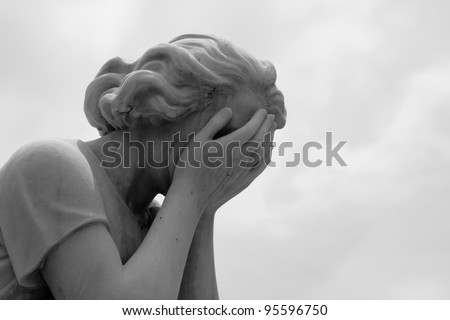 The grief of losing a loved one is captured in a marble statue of a woman crying into her hands.