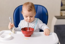 The grimy infant or toddler tries to eat independently. Baby-led weaning. Little child eats himself with a spoon.
