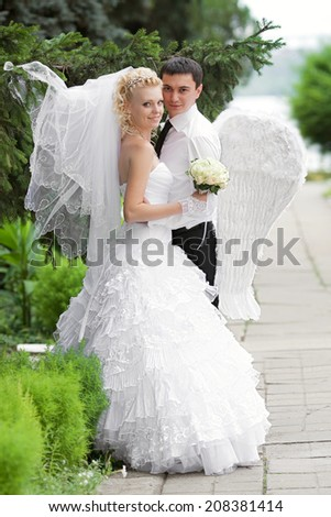 The groom - an angel with white wings and the beautiful bride in their wedding day