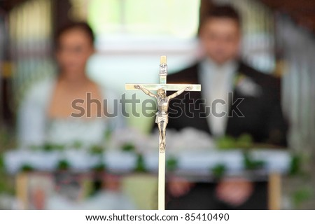 The groom and bride at the wedding ceremony in church - soft focus