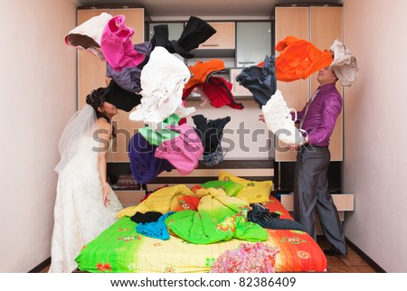The groom and the bride collect things in a bedroom