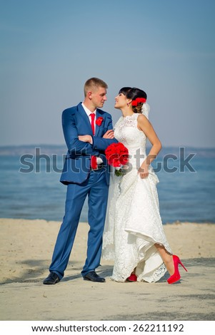 The groom and the bride on a beach (a red bouquet, a red tie, red shoes)