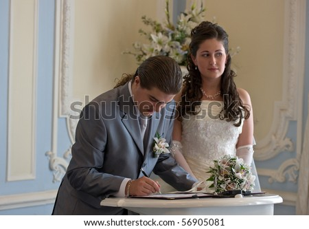 The groom appends the signature in the document of registration of marriage