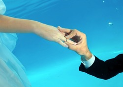 The groom dresses a ring on bride finger under water