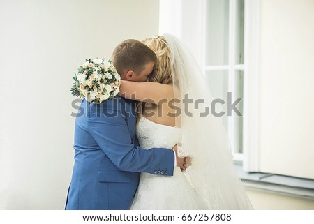 The groom embraces the bride? The groom hugs bride from behind. Woman and man in wedding dress outdoors holding hands. A young man gently embraces his bride in a wedding dress. Wife and husband. #667257808