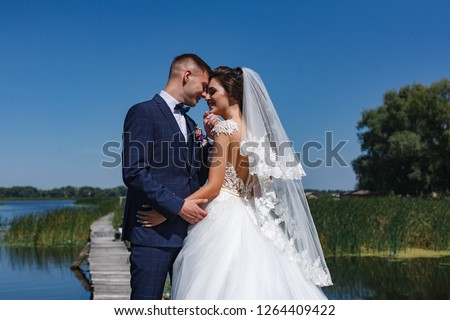 the groom gently kisses the bride in the outdoor Young lovers are happy to walk in nature near river. gentle embrace of brides on the nature Wedding couple walking on bridge near lake #1264409422
