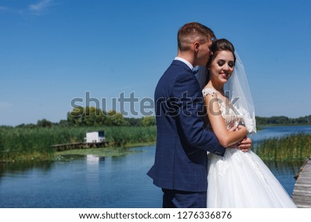 the groom gently kisses the bride in the outdoor Young lovers are happy to walk in nature near river. gentle embrace of brides on the nature Wedding couple walking on bridge near lake #1276336876