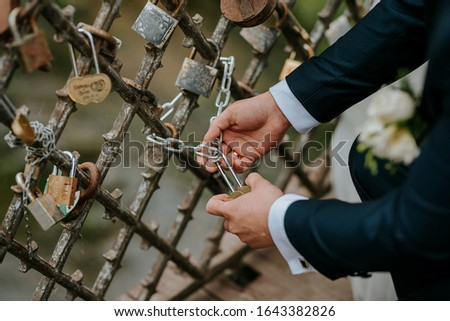 The groom hangs the castle on the bridge