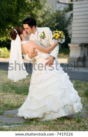 the groom holding and kissing his bride with the bouquet in her hands