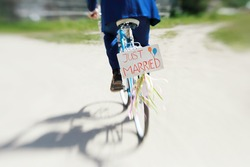 The groom in a blue suit riding a bicycle wedding