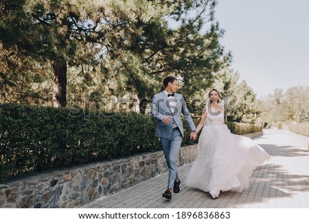 The groom in a gray checkered suit and the blonde bride in a white lace dress run holding hands through the forest, park on the boulevard. Wedding portrait of smiling and emotional newlyweds. ストックフォト ©