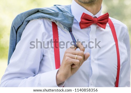 The groom in a white shirt with a red bow tie and in suspenders holds a jacket