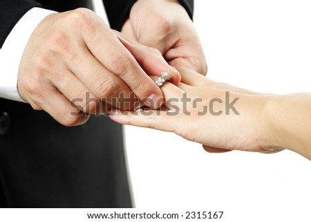 The groom inserting a diamond ring into the bride's finger