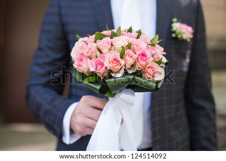 The groom is holding a wedding bouquet
