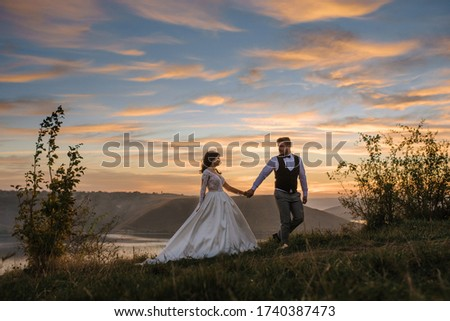 The groom leads the bride by the hand during sunset. Foto stock ©
