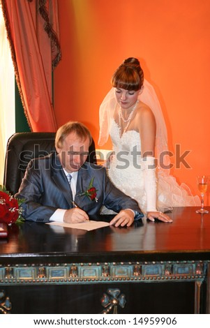 The groom puts the signature in the marriage contract