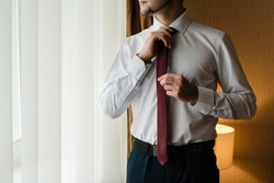 the groom straightens his tie, man in a tie, The morning of the groom, bridegroom's fees, fiance in shirt, claret tie