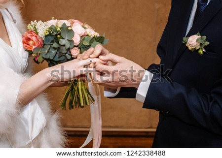 The groom wears a wedding ring to the bride. #1242338488