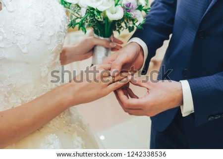 The groom wears a wedding ring to the bride. #1242338536
