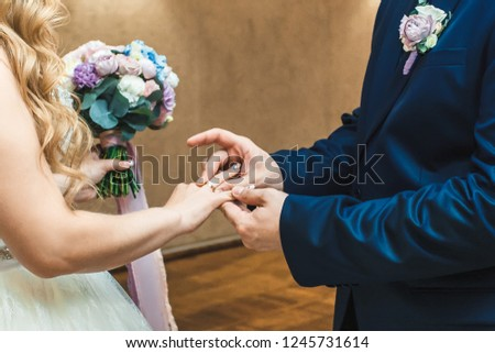 The groom wears a wedding ring to the bride. #1245731614