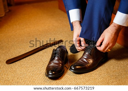 The groom wears his shoes #667573219
