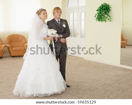 The groom with the bride in a ceremonial hall during wedding