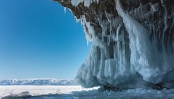 The grotto in the granite rock is covered with bizarre ice splashes, icicles. Arched vault against the blue sky. In the distance, a snow-covered mountain range, the surface of a frozen lake. Baikal