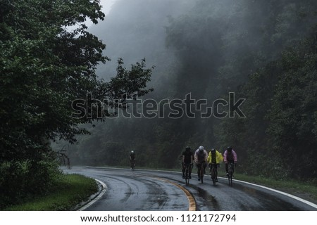 The group of cyclists ride his bicycle up high on hill, Cycling to destination no matter how bad weather is. Foggy, windy, raining and cold day.