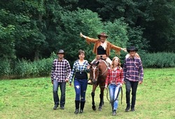 The group of happy smiling people walking with the horse in the nature