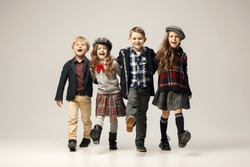 The group of happy smiling teen girls and boys. Sublings day. Stylish young teen girls posing at studio. Classic autumn style. Teen and kids fashion concept. children's fasion concept