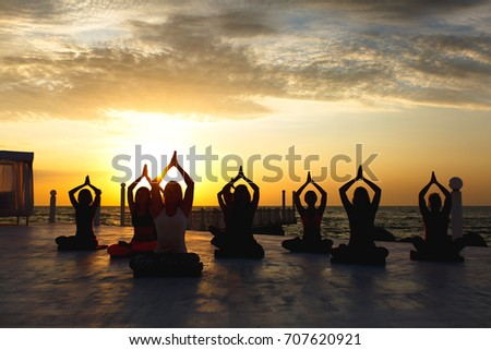 The group of women doing yoga at sunrise near the sea #707620921