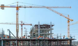 the grouping of workers  are working on construction site,labourers wearing safety helmet,construction crews on site,tower cranes