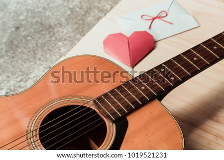 The guitar and red heart fold paper with white envelope. Long distance relationship and love song as a concept.
