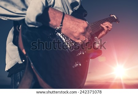 The Guitarist. Guitarist Playing on the Electric Guitar at Sunset. Closeup Photo.
